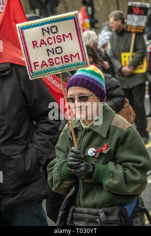 London, UK. 16th March 2019. A woman holds her embroidered placard 'No Racism No Fascism' on the march by thousands through London on UN Anti-Racism day to say 'No to Racism, No to Fascism' and that 'Refugees Are Welcome Here', to show solidarity with the victims of racist attacks including yesterdays Christchurch mosque attack and to oppose Islamophobic hate crimes and racist policies in the UK and elsewhere. The marchers met in Park Lane where there were a number of speeches before marching to a rally in Whitehall. Marches took place in other cities around the world including Glasgow and Car - Stock Image