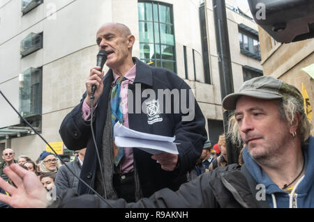 London, UK. 21st December 2018.Donnachadh McCarthy speaks at the Extinction Rebellion protest at the BBC calling it to stop ignoring the climate emergency & mass extinctions taking place and promoting destructive high-carbon living through programmes such as Top Gear and those on fashion, travel, makeovers etc. The protest, organised by the Climate Media Coalition (CMC) and its director Donnachadh McCarthy brought mannequins wrapped in white cloth to the BBC representing the bodies of a Greek village killed by fire. Peter Marshall/Alamy Live News - Stock Image