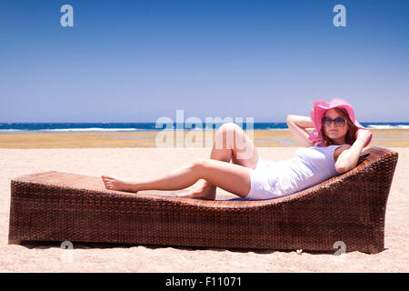 Young woman in a hat relaxes on a lounger on the beach - Stock Image