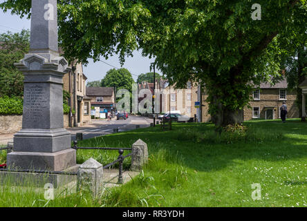 The village green in the pretty Bedfordshire village of Harrold, UK; with the war memorial to the left and the High Street in the middle distance. - Stock Image