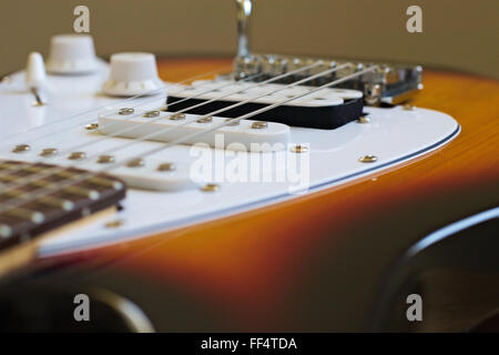 Looking over the bridge and scratchplate of an electric guitar. - Stock Image