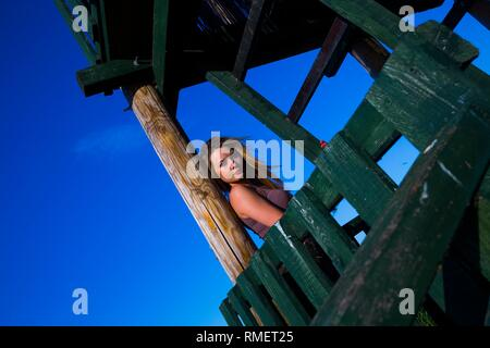 Attractive young woman in nature in sunset evening time standing on wooden observation house building tower structure framework - Stock Image