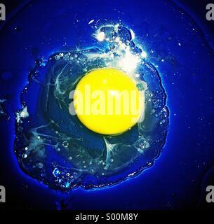 Cracked egg in blue bowl. - Stock Image