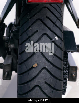Close-up of a nail and a stone embedded in the tread of a tyre. - Stock Image