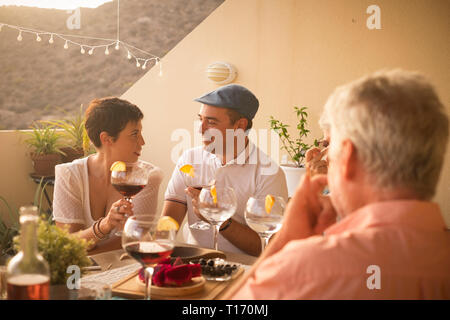 Romantic nice couple in love whisper and enjoy the cocktail time at home with friends - looking in each other eyes for romance and relationship concep - Stock Image