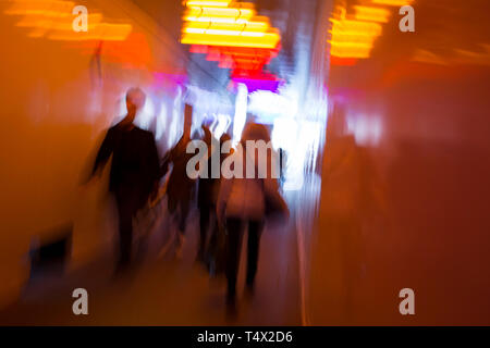 Blurred pedestrians walk through a multi-coloured tunnel under a large construction site in Knightsbridge, on 11th April 2019, in London England. - Stock Image