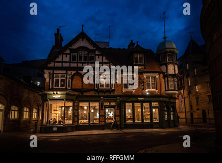 A Tudor building turned into a restaurant in Cambridge town center floodlit at night - Stock Image