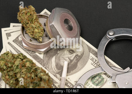 Closeup of marijuana joint on benjamin franklin dollar bill with bud in metal grinder isoalted on black background - Stock Image