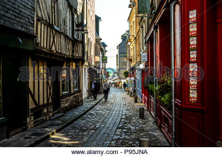 Tourists wander the narrow back streets of the picturesque medieval fishing village of Honfleur on the Normandy coast of France. - Stock Image
