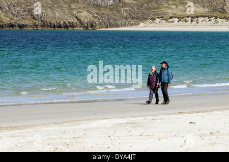 Mature couple walking along a beach in the Western Isles - Stock Image
