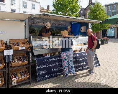 A man and a woman chatting with stallholders on the Little Yorkshire Cheese stall in Ripon Market North Yorkshire England UK - Stock Image