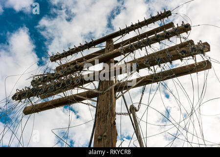 Close-up of the top of an abandoned powerline pole with tangled wires. - Stock Image
