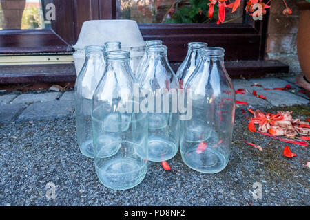 Milk bottles sat outside a front door waiting to be collected by a milkman. - Stock Image