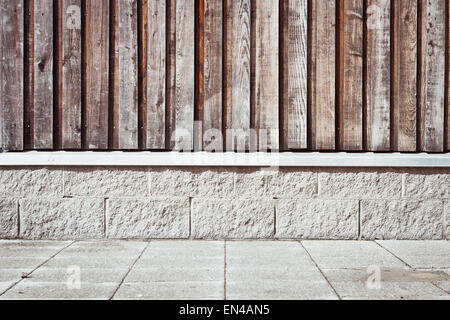 Wooden wall with a brick base on a modern eco building in the UK - Stock Image