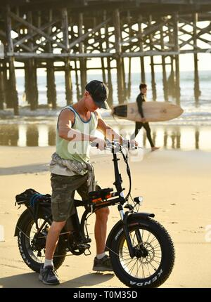 Fit, middle-aged man riding fat tire bicycle biking on beach during sunset at Pacific Beach, San Diego, California, USA - Stock Image