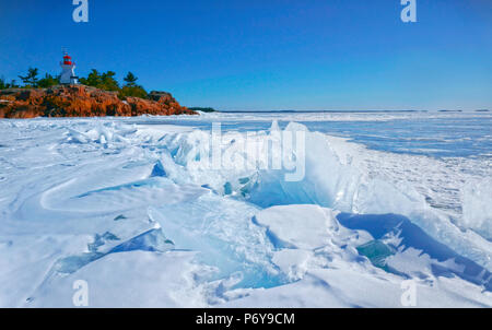 Georgian Bay frozen with ice hunks on solidly frozen water surface with historic lighthouse in Killarney, Ontario, Canada - Stock Image