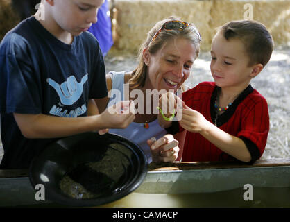 Karen Harris, of Sacramento, looks at her sons, Luke, 9, left, and Jake, 4, right, as they pan for gold during gold - Stock Image