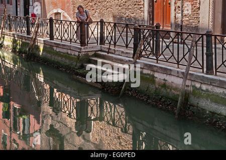 Lady looking down at reflections in rio by Ponte Zaguri near Campiello de la Feltrinella in Venice Italy - Stock Image