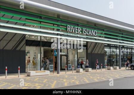 Exterior of River Island, a fashion retailer; Rushden Lakes Shopping Centre, Northamptonshire, UK - Stock Image