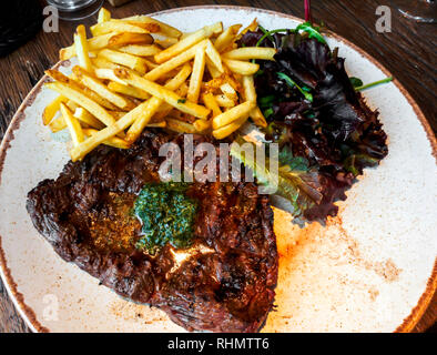 Lunchtime flattened pan-seared bavette Steak served with French fried potatoes and rocket salad - Stock Image