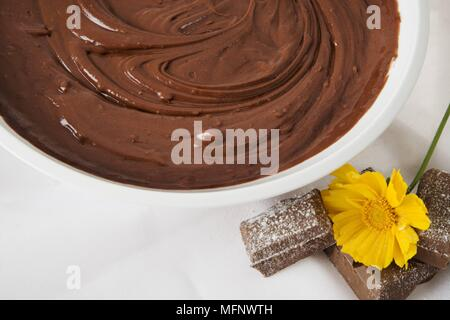 Chocolate mix in a white bowl with yellow flower. Studio shot.         Ref: CRB538_103609_0027  COMPULSORY CREDIT: Martin Harvey / Photoshot - Stock Image