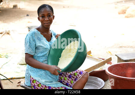 Abidjan, côte d'ivoire - February 22, 2017: a young girl seated on a stool in a sky-blue dress, holding a green bowl full of cassava flour is stirring - Stock Image