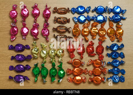 A selection of foil wrapped sweets layed out on a wooden table - Stock Image