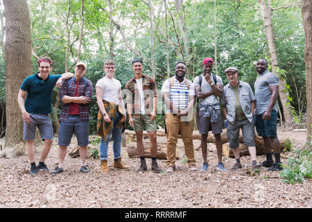 Portrait confident mens group hikers standing in a row in woods - Stock Image