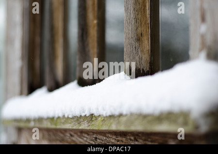 Snow settled on the bottom of a wooden window frame - Stock Image