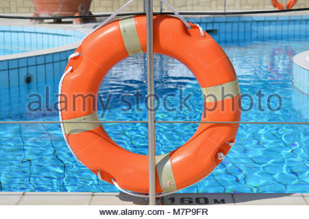 Orange coloured life ring attached to rope fence at the side of a swimming pool in sunlight - Stock Image