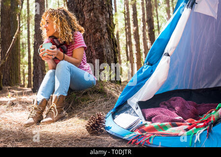 Pretty caucasian middle age woman sitting on the ground doing camping with tent in the forest and enjoying the outdoor leisure activity - alternative  - Stock Image