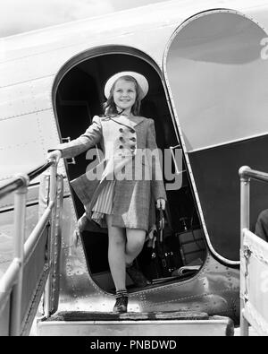 1940s SMILING GIRL STEPPING OFF OF AMERICAN AIRLINES PASSENGER PLANE ARRIVING DISEMBARKING - a1479 HAR001 HARS AIRLINES STYLISH DISEMBARKING CONFIDENT FASHIONS JUVENILES PRE-TEEN PRE-TEEN GIRL BLACK AND WHITE CAUCASIAN ETHNICITY HAR001 OLD FASHIONED - Stock Image