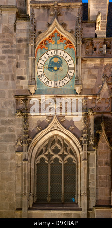Astronomical clock near north entrance to Autun Cathedral with evening light and floodlights - Stock Image