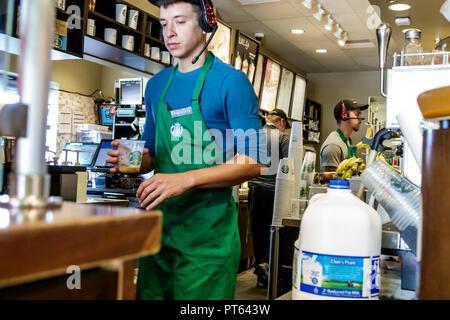 Sebring Florida Starbucks Coffee cafe inside barista behind counter employee working man - Stock Image