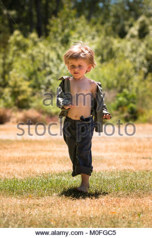 Little boy running on a field - Stock Image