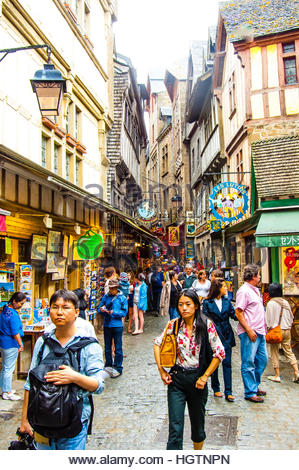 Views & sites around the town and Island of Mont St Michel in Normandy, France. Tourists walk up the packed - Stock Image