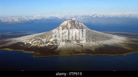 A small steam plume rises from the snow-covered lava dome at the summit of Augustine Volcano on Augustine Island - Stock Image