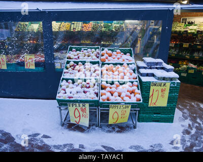 Snow covered crates of apples, oranges and grapes outside a greengrocers shop in Oslo Norway in the winter - Stock Image