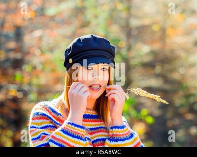 Young woman teen girl female adolescent and warm Autumn colors in nature portrait head and shoulders looking at camera - Stock Image