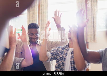 Men praying with arms raised in prayer group - Stock Image