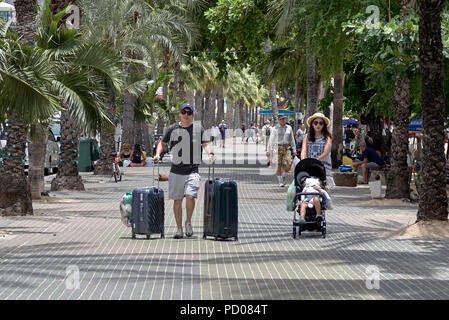 Young family on holiday walking along the street with suitcases and child in pushchair - Stock Image