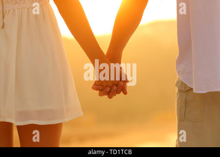 Close up portrait of a couple holding hands walking at sunset - Stock Image