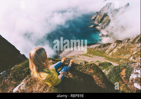 Summer vacations in Norway travel woman tourist relaxing alone on mountain cliff over ocean active lifestyle hiking adventure outdoor - Stock Image