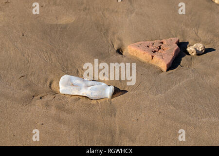Plastic bottle and pieces of foam washed up from the Atlantic Ocean on Agadir beach, Morocco, Africa - Stock Image