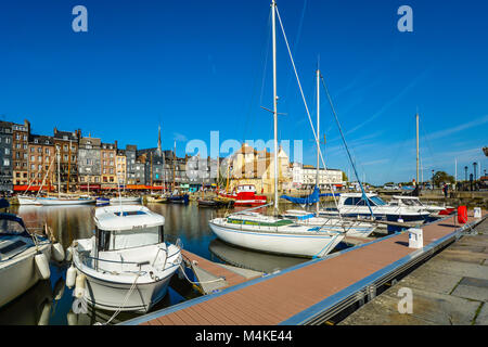 Boats, yachts and sailboats, line the old harbour at Honfleur France in Normandy surrounded by slate covered homes, - Stock Image