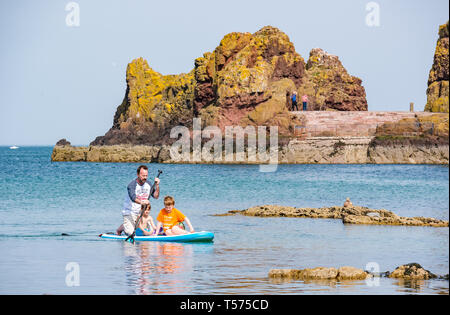 Dunbar, East Lothian, Scotland, UK. 21st Apr 2019. UK Weather:  People enjoy the very sunny hot Easter day weather at Eye Cave cove. A father and children paddle boarding - Stock Image