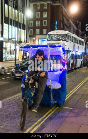 bicycle taxi parked at dusk on a London street whilst the rider uses his mobile phone. - Stock Image