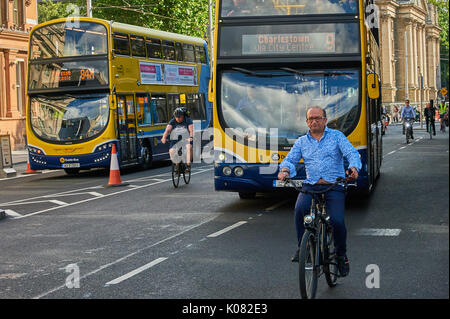 Public transport and cyclists on a street in Dublin city centre - Stock Image