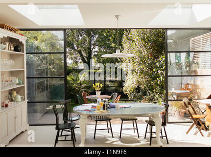 Kitchen table and patio doors open to sunny garden - Stock Image