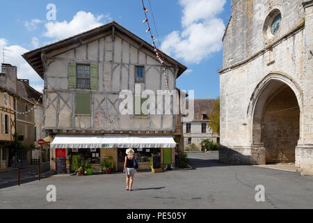A tourist looking at a shop and the church; Issigeac , a bastide town in the Dordogne, France Europe - Stock Image